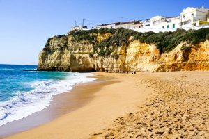 Beautiful Places in Portugal - Beach with cliffs and whitewashed buildings.
