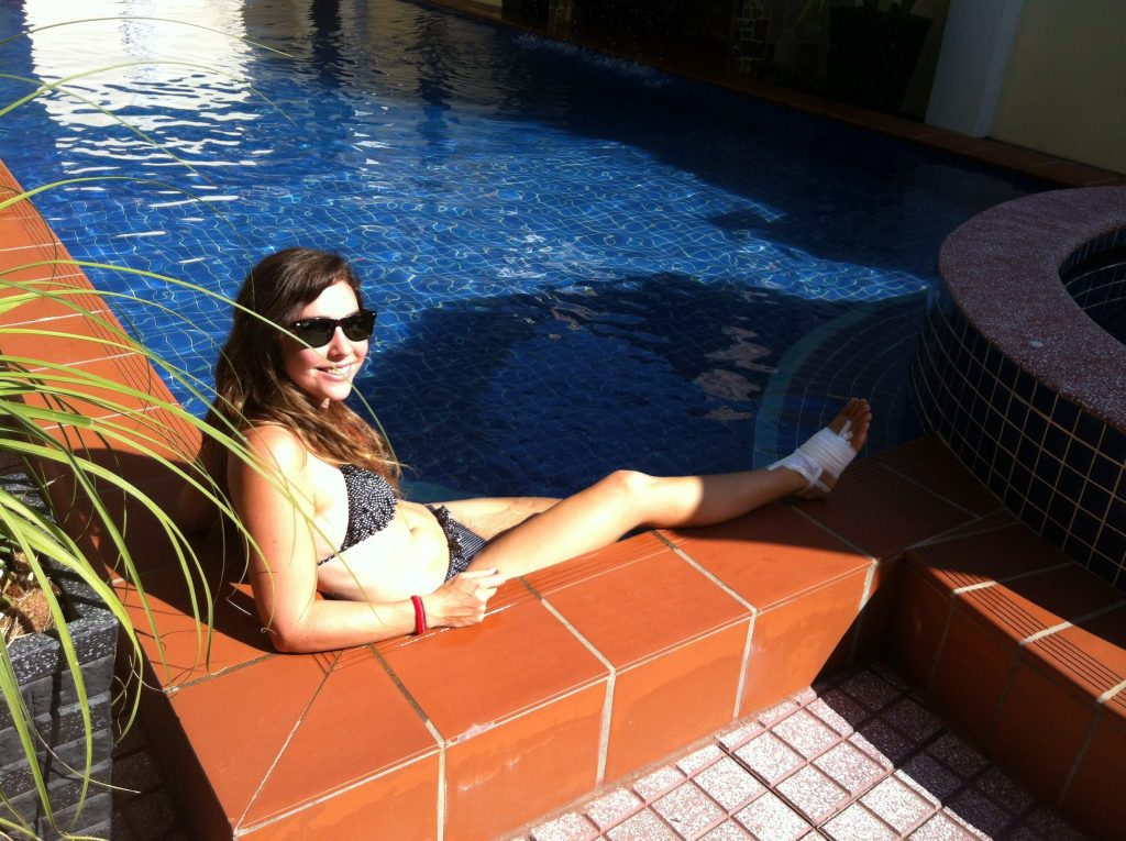 Travel insurance tips - girl in pool with injured foot