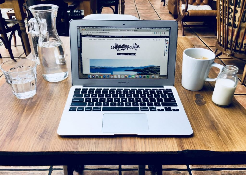 How to Find your Blogging Niche - Laptop on table with coffee and water