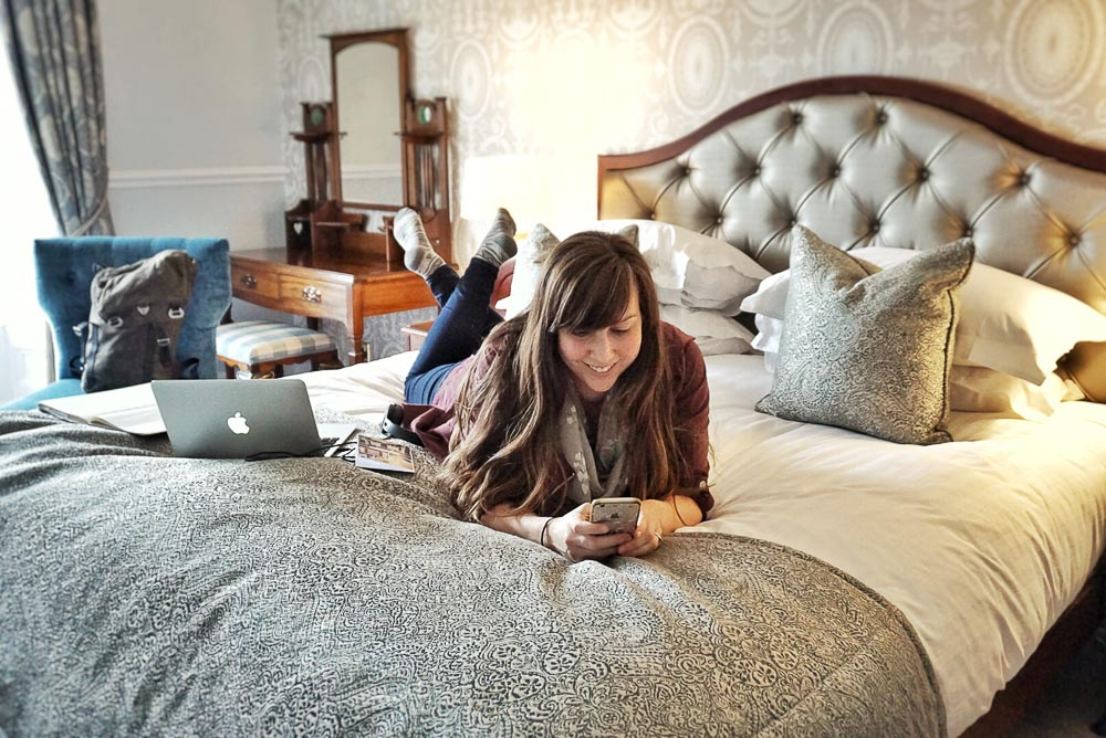 How to Find your Blogging Niche - Lying on hotel bed working on phone with laptop