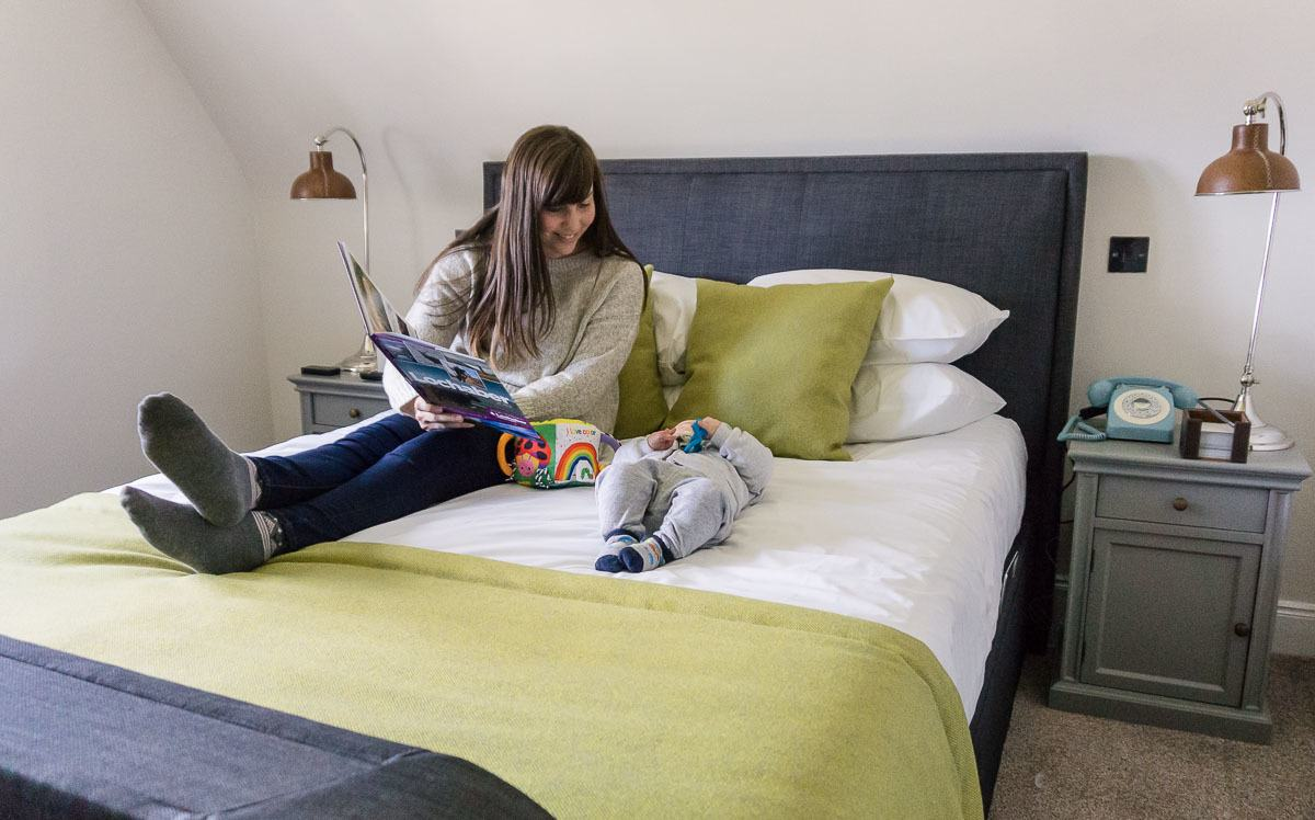 Mother reading a book to baby on hotel bed