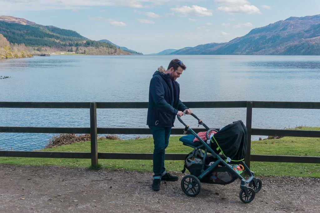 Man with pram in front of lake and mountains in Scotland