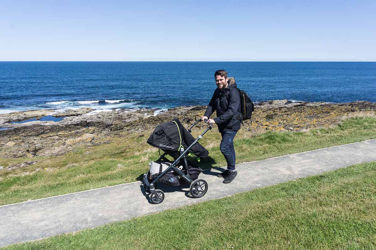 Pushing pram along path by the sea