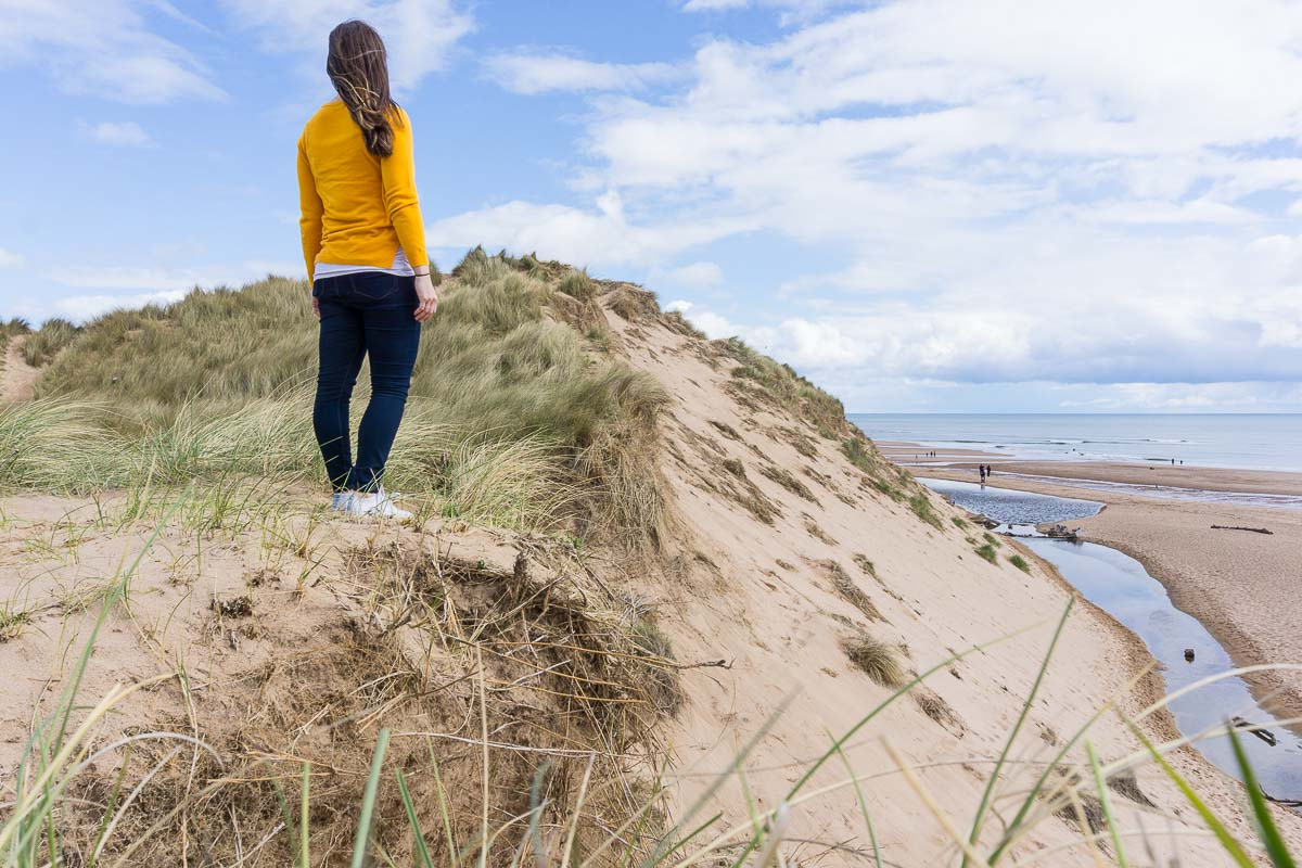 Solo Travel Destinations: Woman standing on sand dune in Scotland