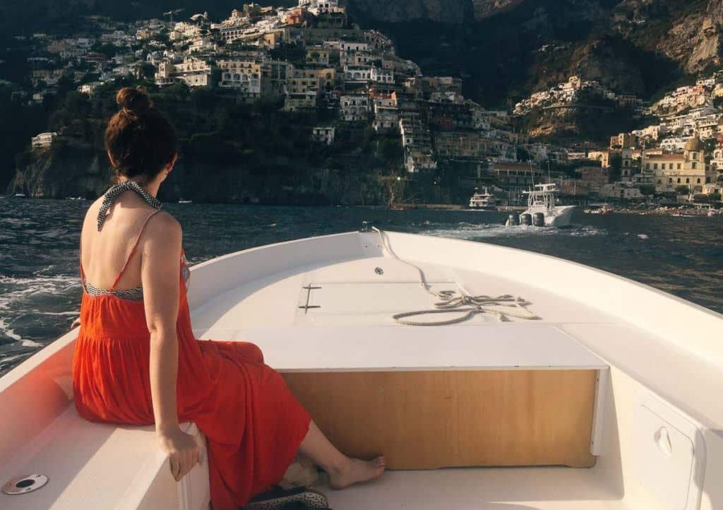 Babymoon Destinations Europe - Amalfi Coast - On boat in red dress looking at coastal village.
