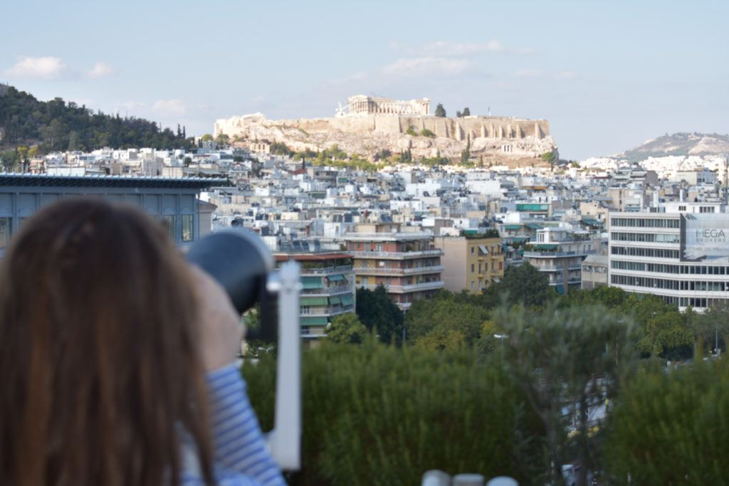 Babymoon Destinations Europe-Athens - Woman taking a photo of Acropolis from a distance