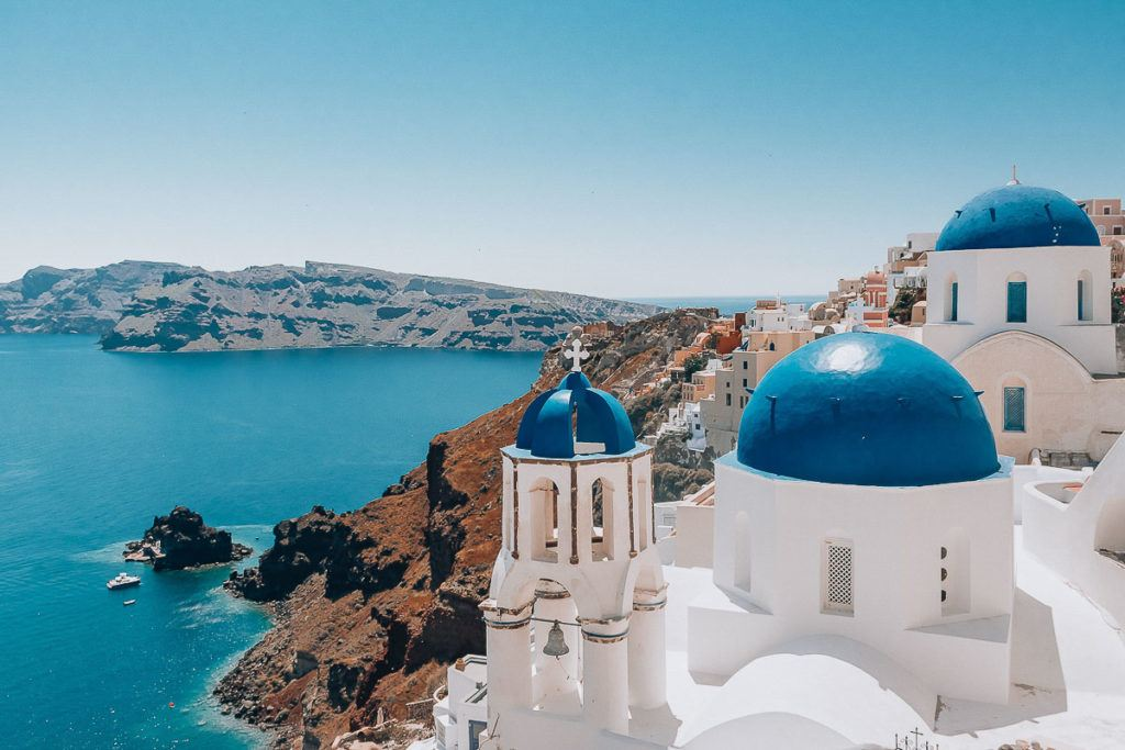 Babymoon Destinations Europe-Santorini - Blue and white buildings on cliff overlooking ocean
