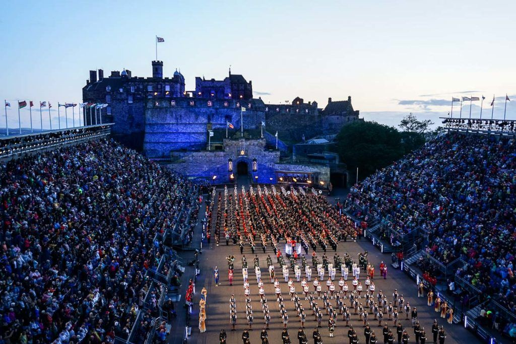 Edinburgh Military Tattoo - Scotland Flag on Edinburgh Castle and Military Bands and Dancers in lines on forecourt