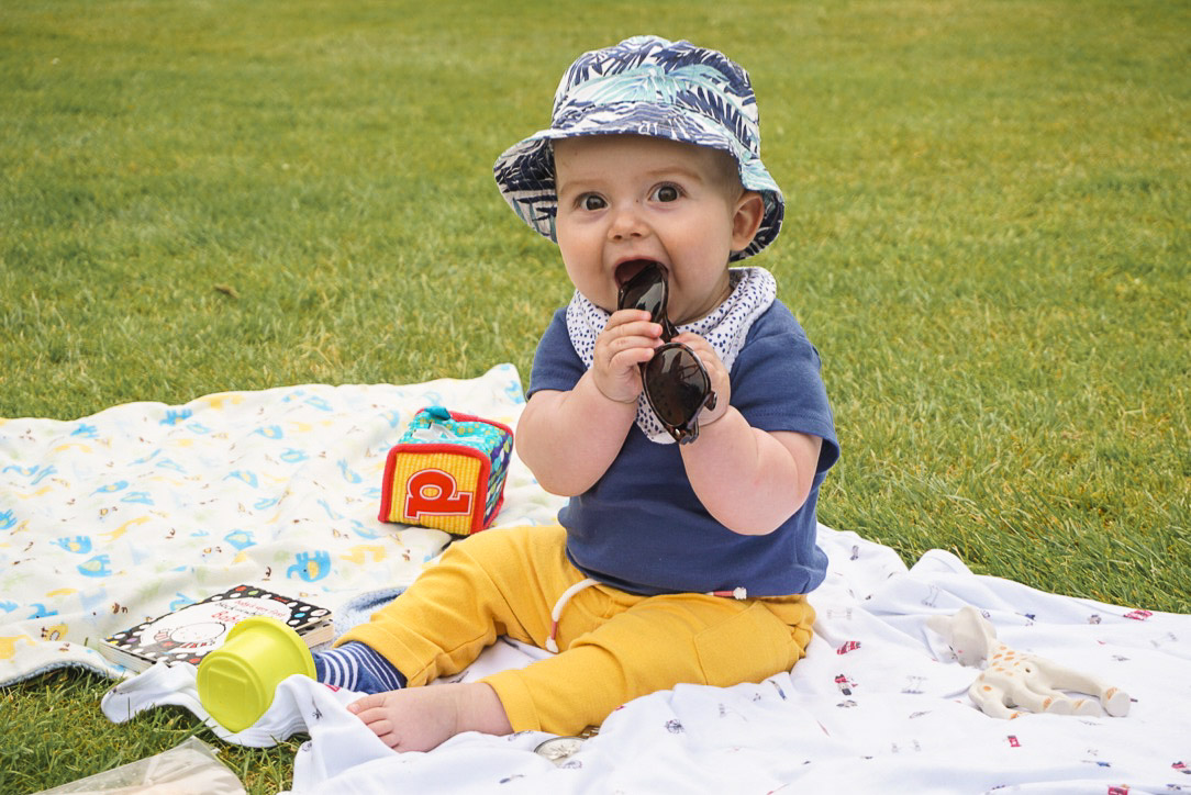 Baby on blanket on grass with toys