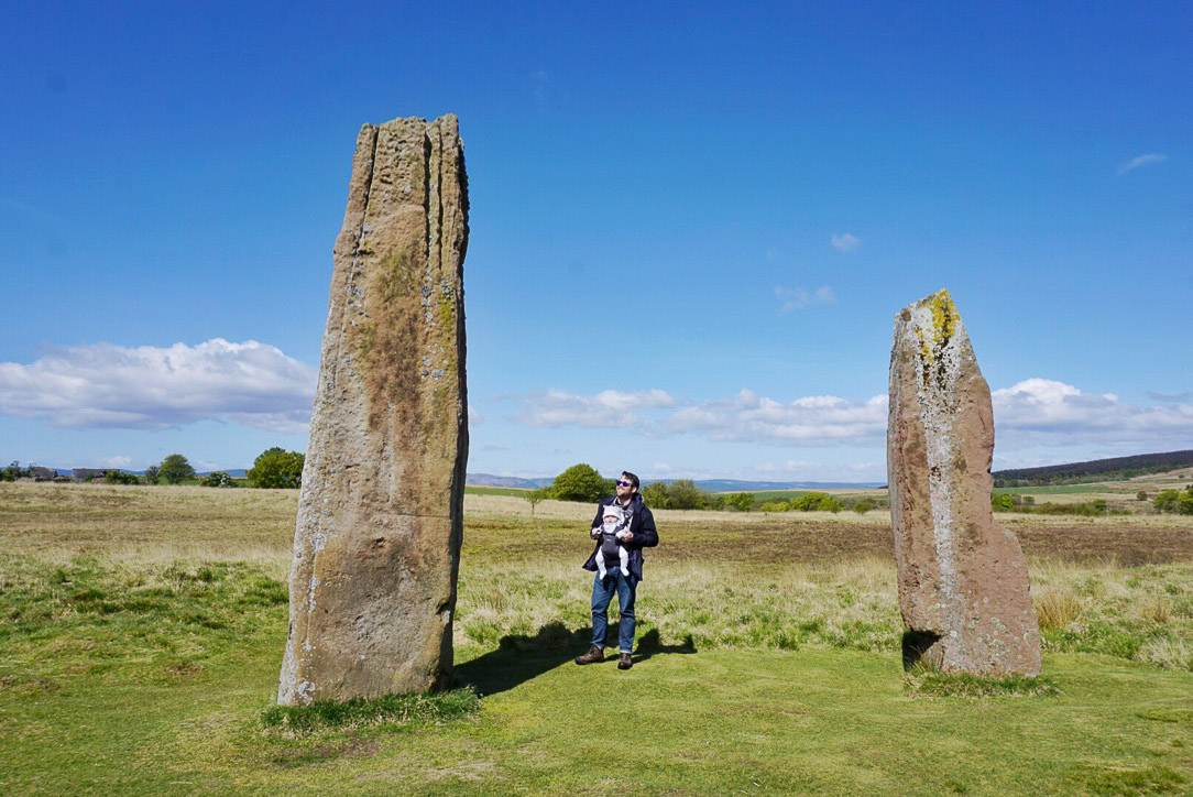 Standing stones in field and man with baby