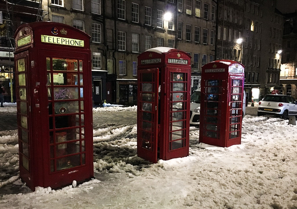 Royal Mile in Edinburgh in Winter with snow and red phone boxes