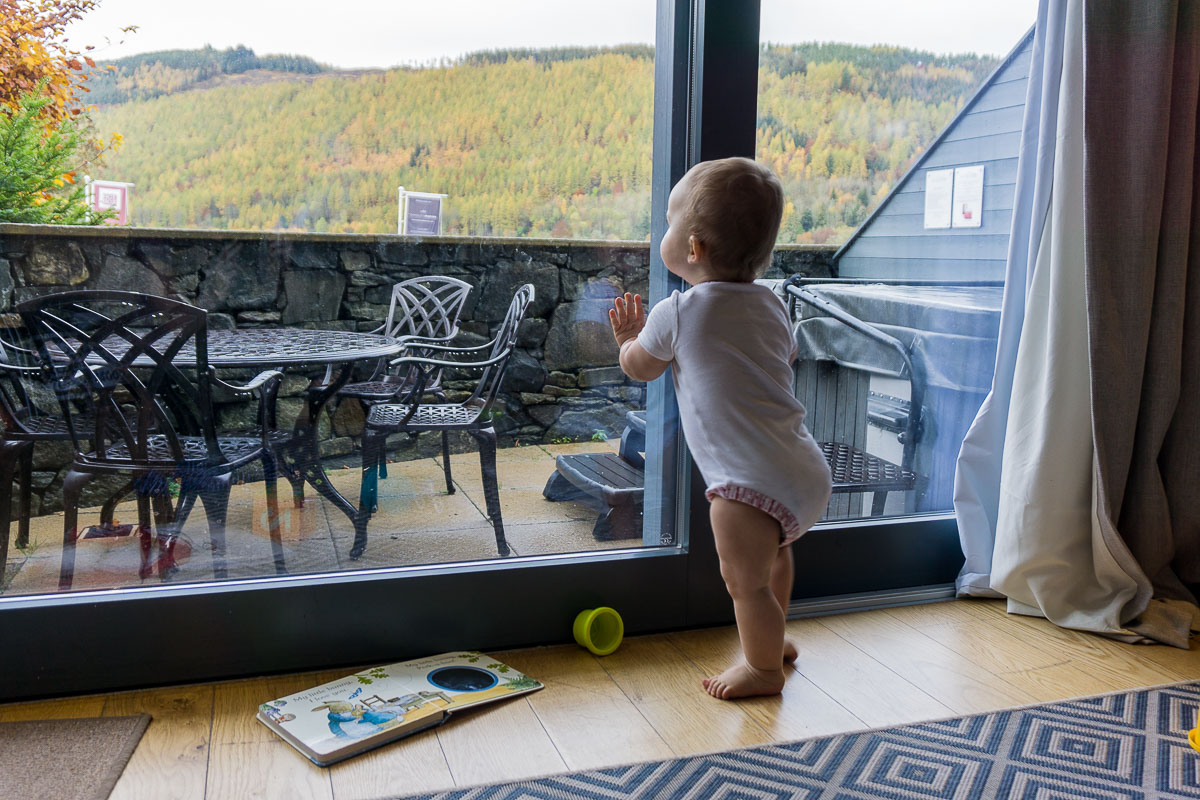 Baby looking out window at Taymouth Marina apartment