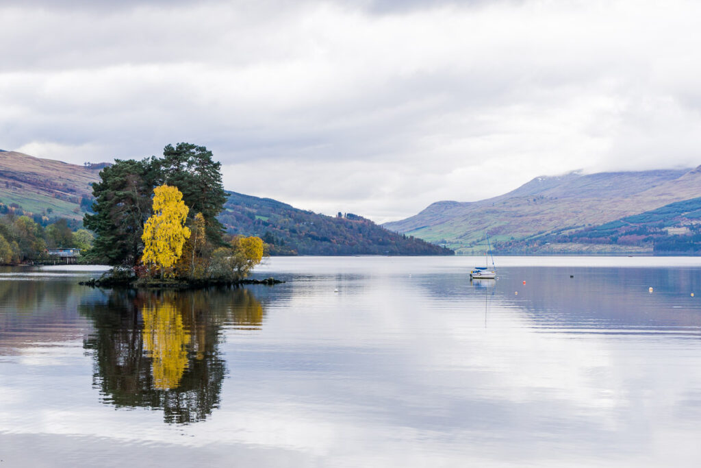 Calm lake with island with multicoloured autumn trees, Loch Tay Perthshire Scotland