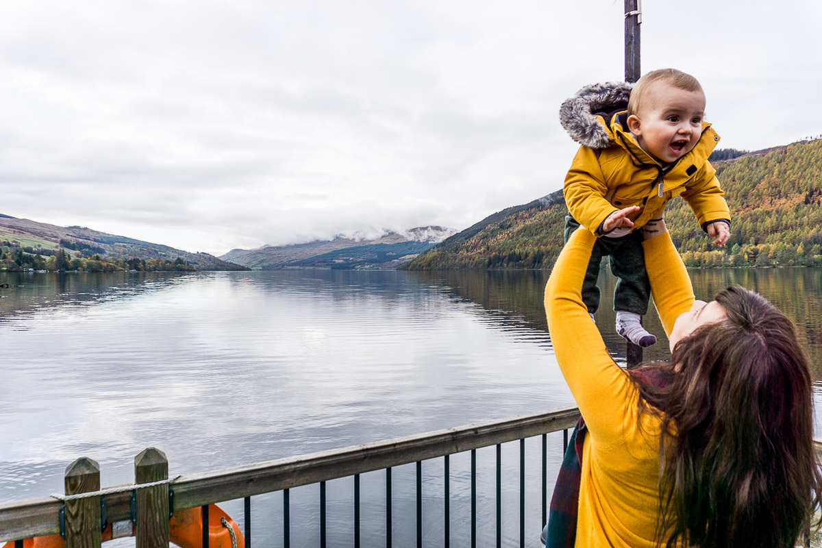 Mum lifting up baby overlooking Loch Tay