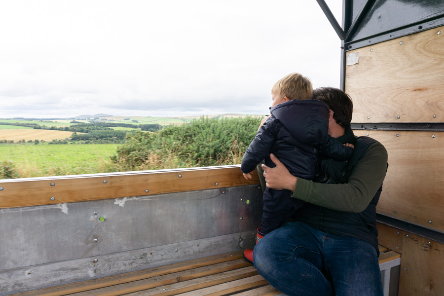 Jackons at Jedburgh - Toddler and father on trailer overlooking farmland