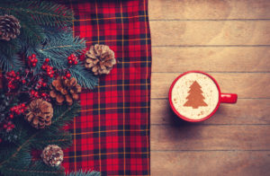 Tartan and pinecones on a table with cappucino - Scottish Christmas Traditions