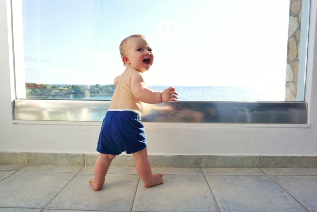 Best Greek Islands for Families - Baby on hotel balcony looking out at sea