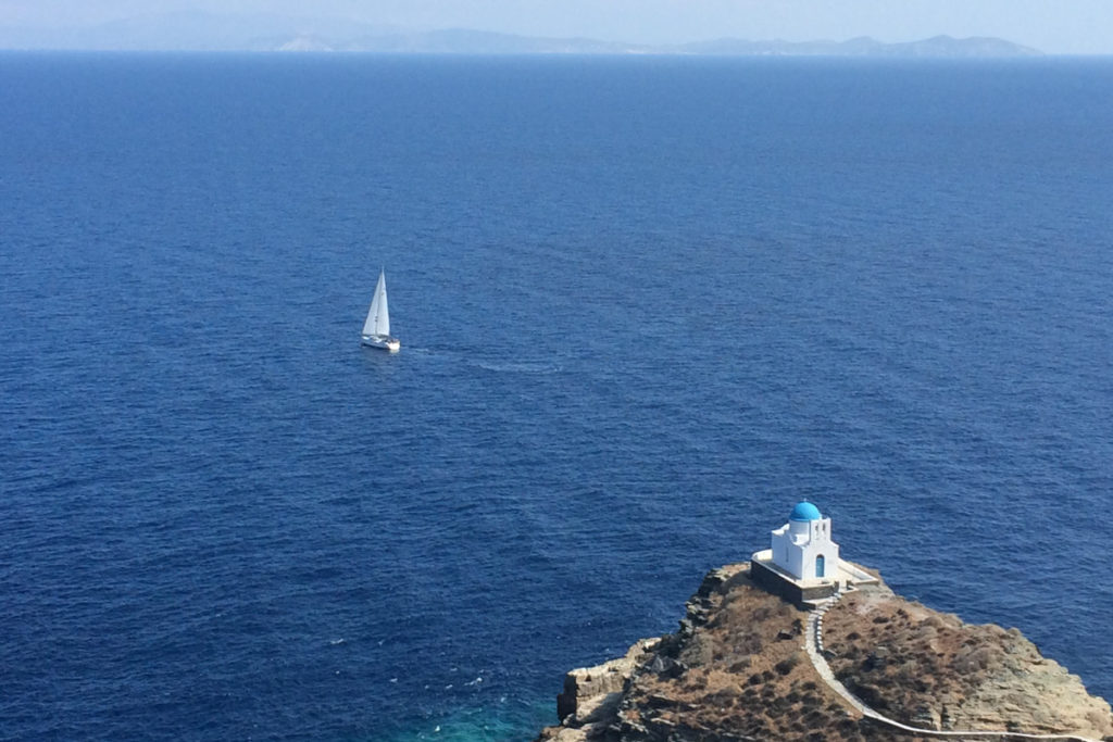 Best Greek Islands for Families - Church and sea with sailboat in Sifnos
